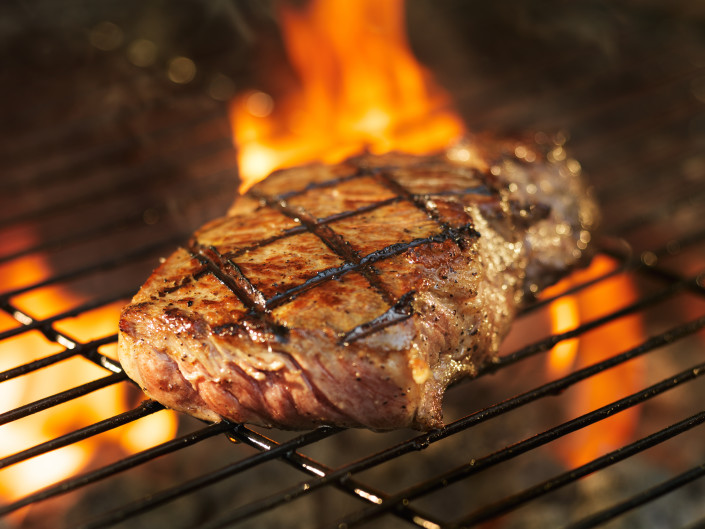 ribeye steak cooking on grill